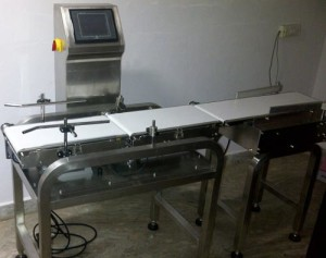 Checkweigher is designed for fast, accurate weight control of cases, bulk bagged products, corrugated boxes, or other large Containers. It consists of a versatile strain gage weightable system mounted on a sturdy, welded, all-steel frame. Conveyor belt moves packages for instant weighing. The solid, extruded polyester resin, smooth finish belt wears better, cleans up faster, and lasts longer.